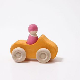 gelbes Holzauto mit rosa Holzfigur