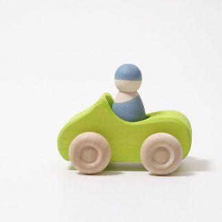 grünes Holzauto mit blauen Holzfigur